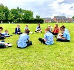 pupils sitting in a circle on grass